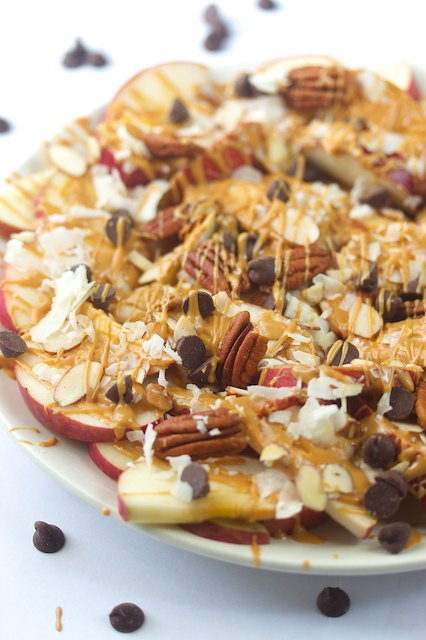 crisp apple slices drizzled with peanut butter and topped with pecans, coconut flakes and chocolate chips